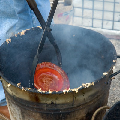 raku firing - heated ware being plunged into the reducing agent